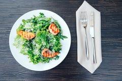 Pesce arrostito ed insalata verde fresca su un piatto bianco Priorità bassa di legno Vista superiore immagine stock
