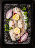 Pesce crudo con le spezie, l'erba, la mezza cipolla, il limone ed il sale sul fondo scuro del vassoio della protezione fotografia stock libera da diritti