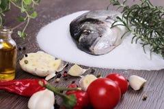 Pesce crudo fresco dell'orata su sale decorato con il limone e le erbe su fondo di legno blu Concetto sano dell'alimento Immagine Stock