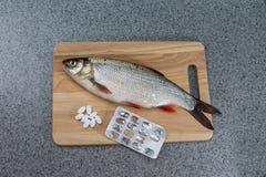 Pesce crudo, non cucinato Pesce bianco su un tagliere e sulle pillole Immagini Stock Libere da Diritti