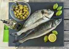 Pesce crudo pronto da cucinare due con il limone e le olive sull'ardesia di pietra Immagini Stock