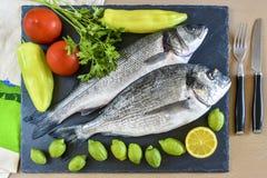 Pesce crudo pronto da cucinare due con il limone ed i pomodori sulla stecca di pietra Fotografia Stock