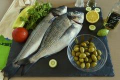Pesce crudo pronto da cucinare due con le verdure sul bordo di pietra dell'ardesia Immagine Stock Libera da Diritti