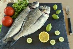 Pesce crudo pronto da cucinare due con le verdure sul bordo di pietra dell'ardesia Immagine Stock