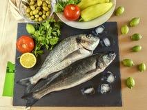 Pesce crudo pronto da cucinare due con le verdure sul bordo di pietra dell'ardesia Fotografia Stock