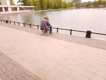 Pesce dei fermi del pescatore nello stagno della città Fotografia Stock