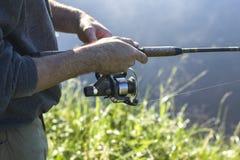 Pesce dei fermi del pescatore per filare Tira la linea di pesca con una filare-ruota Fotografie Stock Libere da Diritti