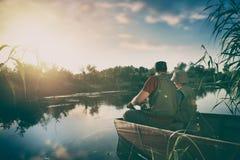 pesce del fermo del figlio e del padre da una barca al tramonto fotografia stock