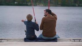 Pesce del figlio e del padre sul lago stock footage