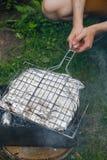 Pesce della frittura dell'uomo in una stagnola su una griglia Fotografia Stock