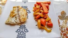 Pesce di Barramundi, fritto, accanto al lato delle cipolle arrostite e delle carote immagini stock