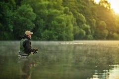 Pesce di caccia del pescatore di sport Pesca all'aperto nel fiume fotografie stock