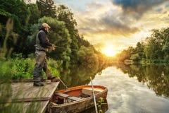 Pesce di caccia del pescatore di sport Pesca all'aperto nel fiume immagini stock libere da diritti