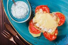 Pesce di color salmone cotto con gamberetto, formaggio, i pomodori, la melanzana e la salsa su fondo di legno fotografia stock