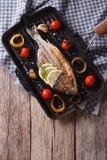 Pesce di Dorado che cucina sul primo piano della leccarda Vista superiore verticale Immagine Stock