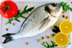 Pesce di mare con le spezie, i pomodori rossi, il limone e le erbe immagini stock libere da diritti