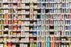 Pesce e carne inscatolati sugli scaffali del supermercato Immagine Stock Libera da Diritti