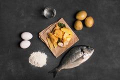 Pesce e patate fritte britannico tradizionale sulla superficie scura Immagini Stock Libere da Diritti