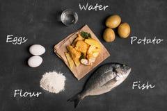 Pesce e patate fritte britannico tradizionale sulla superficie scura Fotografie Stock