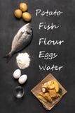 Pesce e patate fritte britannico tradizionale sulla superficie scura Immagine Stock Libera da Diritti