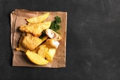 Pesce e patate fritte britannico tradizionale sulla superficie scura Fotografia Stock Libera da Diritti