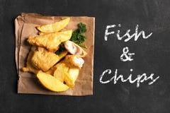Pesce e patate fritte britannico tradizionale sulla superficie scura Fotografie Stock Libere da Diritti
