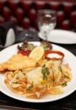 Pesce e patate fritte in piatto Immagini Stock Libere da Diritti