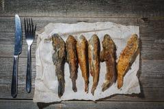 Pesce essiccato con la forcella e coltello sulla tavola Fis asciutti salati del fiume Fotografia Stock