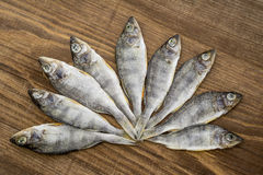 Pesce essiccato su fondo di legno Fotografie Stock