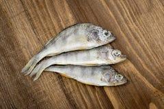 Pesce essiccato su fondo di legno Fotografia Stock