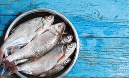 Pesce fresco in ciotola del ferro su un fondo di legno Fotografie Stock