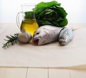 Pesce fresco con aglio, rosmarini e olio d'oliva Immagini Stock Libere da Diritti