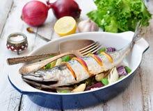 Pesce fresco dello sgombro al forno con un limone, un arco, un sale e un pepe su una tavola di legno Immagini Stock