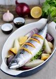 Pesce fresco dello sgombro con un limone, un arco, un sale e un pepe su una tavola di legno Immagine Stock Libera da Diritti
