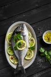 Pesce fresco di Dorado con il limone, la limetta ed il prezzemolo su un piatto ovale immagini stock libere da diritti