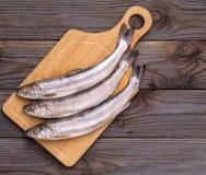 Pesce fresco sul bordo Su una priorità bassa di legno immagini stock libere da diritti