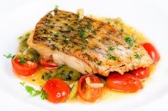 Pesce fritto con i pomodori ciliegia arrostiti Immagini Stock Libere da Diritti