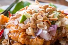 Pesce fritto nel grasso bollente completato con l'arachide e l'erba Immagini Stock