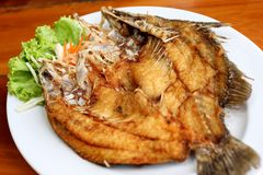 Pesce fritto nel grasso bollente con le verdure sul piatto bianco Immagini Stock Libere da Diritti