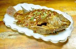 Pesce fritto nel grasso bollente del mango che condisce la salsa di peperoncino rosso dolce sul piatto fotografia stock