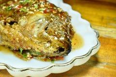Pesce fritto nel grasso bollente del mango che condisce la salsa di peperoncino rosso dolce sul piatto fotografie stock