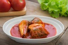 Pesce inscatolato in salsa al pomodoro sul piatto fotografia stock