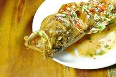Pesce legato rosso fritto nel grasso bollente della cernia che condisce la salsa di peperoncino rosso dolce sul piatto fotografia stock libera da diritti