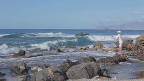 Pesce lussuoso dei cautchs del pescatore al mare pesca Panorama dalle pietre stock footage