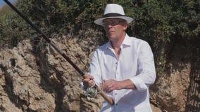 Pesce lussuoso dei cautchs del pescatore al mare Vicino alle rocce pesca video d archivio