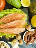 Pesce rosso, avocado, essere a dieta antiossidante naturale su un fondo di legno nero, alimento sano dell'insalata matta del kiwi fotografia stock
