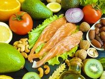 Pesce rosso, avocado, essere a dieta antiossidante su un fondo di legno nero, alimento sano dell'insalata matta del kiwi fotografia stock libera da diritti