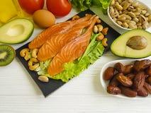 Pesce rosso, avocado, ingrediente sano antiossidante matto della proteina del limone su un fondo di legno fotografia stock libera da diritti