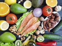 Pesce rosso, cetriolo matto della cena di selezione dell'avocado su alimento di legno e sano nero fotografie stock libere da diritti