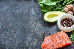 Pesce rosso con le spezie, i verdi e l'avocado su fondo di pietra grigio Fotografia Stock